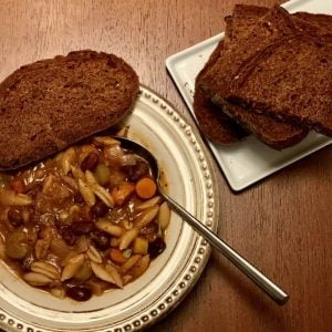 Bowl of minestrone soup with slices of pumpernickel bread
